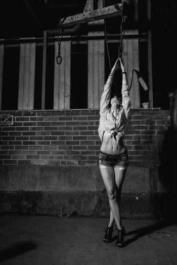 Female Model Posing Against Wall At Night