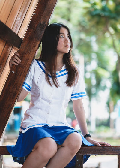Real People Sitting Three Quarter Length Casual Clothing One Person Wood - Material Focus On Foreground Leisure Activity Lifestyles Young Adult Long Hair Day Young Women Women Hair Looking Hairstyle Looking Away Brown Hair Outdoors Beautiful Woman Teenager
