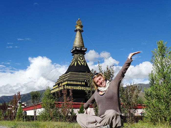 Portrait of woman with arms outstretched with buddhist stupa in background at samye monastery