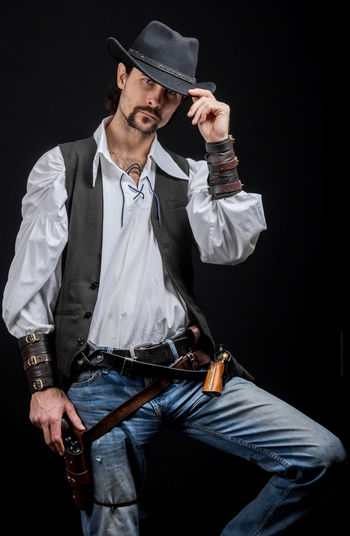 Handsome young man. This is an American cowboy. A vow to a white shirt, brown waistcoat and blue jeans. Black shoes on the feet. Carries a shtyapa, on a belt two pistols. The hair is of medium length; on the face is a beard and mustache. Authentic photo. Culture of America. Cowboy Wild West America American Gun National Authentic Moments Lifestyles Lifestyle One Person Candid Authentic Three Quarter Length Clothing Black Background Front View Men Hat Weapon Holding Young Adult Males  Young Men Handgun Jeans