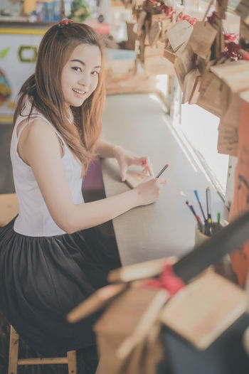 Portrait of smiling young woman sitting in store
