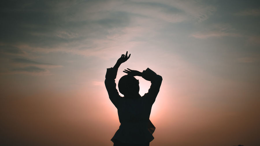 Silhouette woman with arms raised standing against sky during sunset
