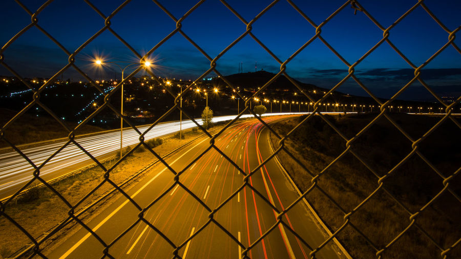 High angle view of light trails on highway seen through chainlink fence at night