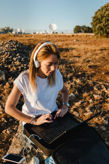 Young woman using laptop sitting on land against sky