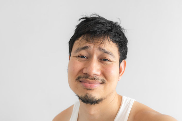 Close-up portrait of smiling mid adult man against white background