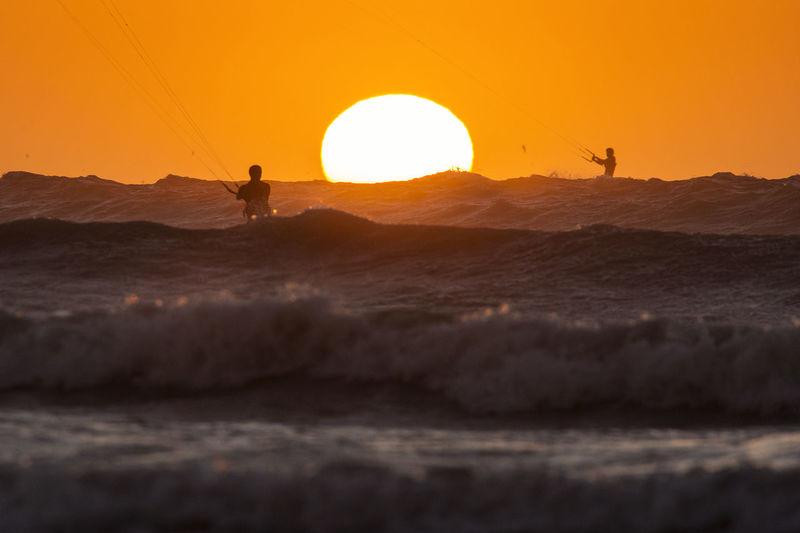 People kiteboarding on sea against sky