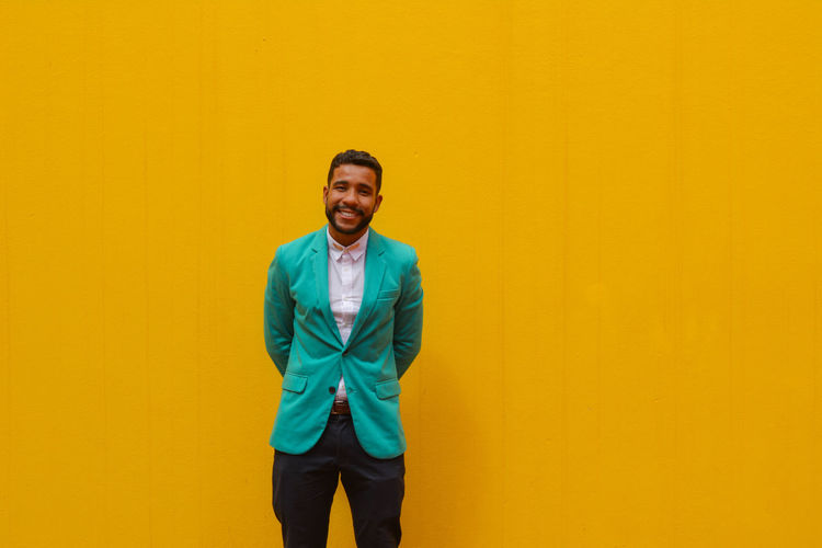 Portrait Of Smiling Young Man Standing Against Yellow Wall
