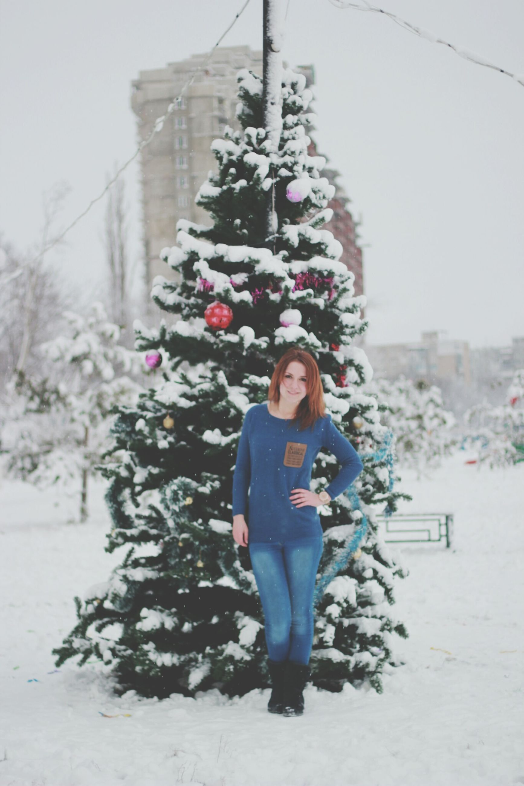 lifestyles, leisure activity, winter, casual clothing, season, snow, warm clothing, cold temperature, person, standing, full length, flower, focus on foreground, front view, building exterior, built structure, day, holding