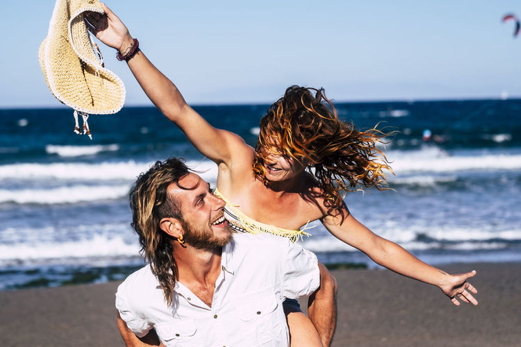 Man piggybacking cheerful woman at beach against sky