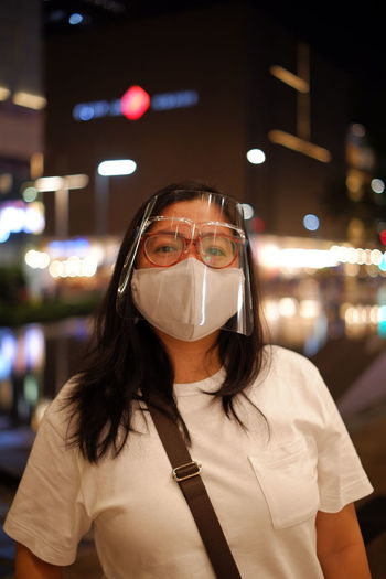 Portrait of young woman wearing face mask standing outdoors
