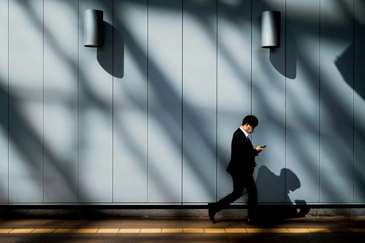 Side view of a man walking on wall