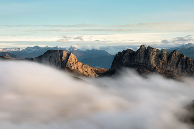 Mountains in fog at sunset in autumn. landscape with alpine mountain valley, low clouds