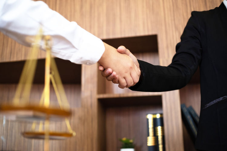 Midsection of business people shaking hand in office