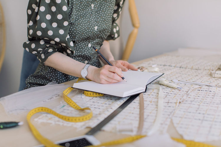 Midsection of woman writing in book at table