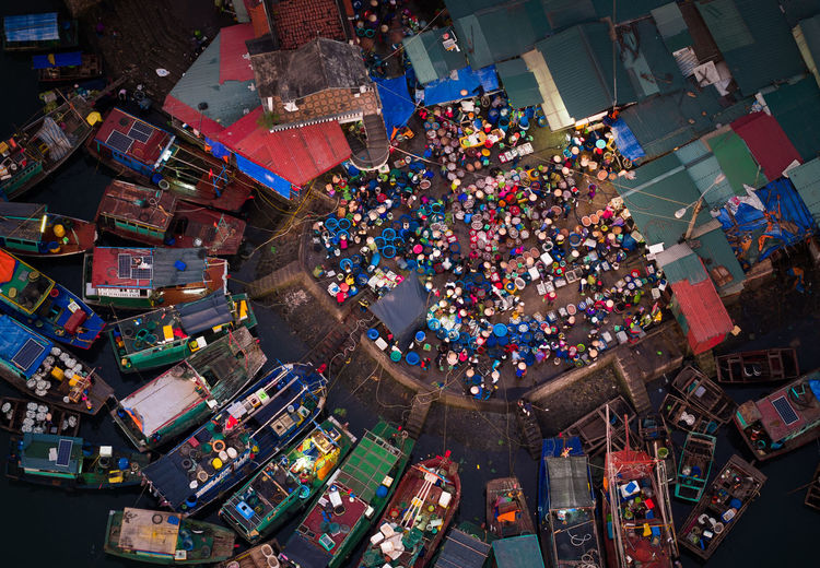 High Angle View Of Market In Town By Moored Boats In River