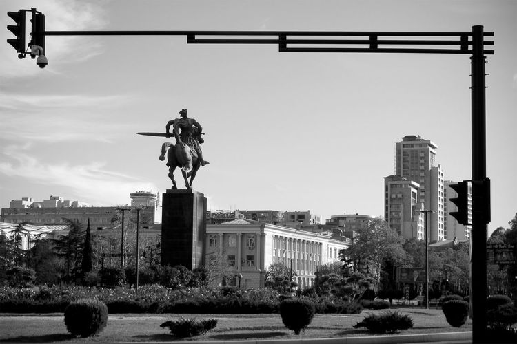 Statue in city against sky
