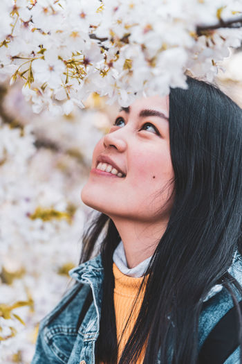 Smiling young woman looking at blooming flowers
