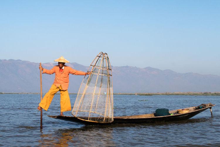 Balance Balancing Act Burma Day Fisherman Fishing Fishing Boat Fishing Tools Hat Inle Lake Lake Myanmar Nature Net Orange Clothes Outdoors People Sky Standing Tradition Traditional Clothing Water