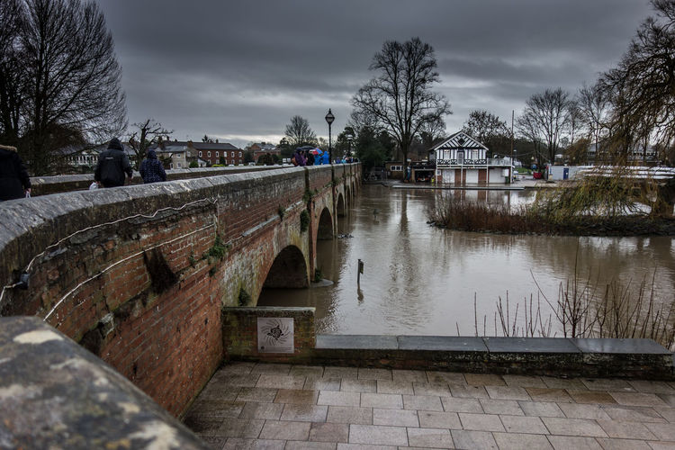 Arch bridge over river against cloudy sky at stratford-upon-avon