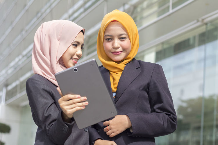 Adult Communication Connection Digital Tablet Focus On Foreground Front View Hijab Holding Lifestyles Outdoors People Real People Smiling Standing Technology Two People Waist Up Wireless Technology Women Young Adult Young Women