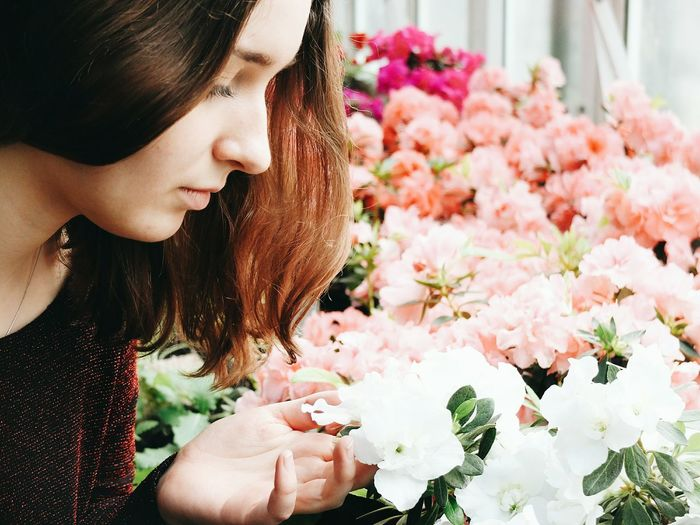 Young woman examining flowers at shop