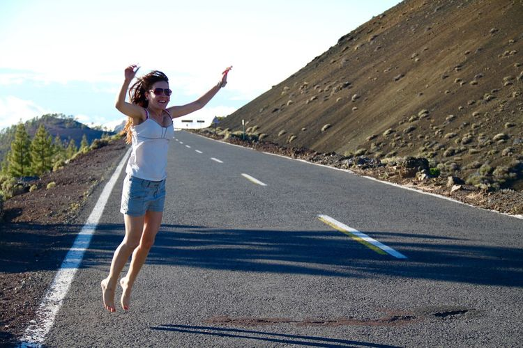 Full length of cheerful woman jumping with arms raised on road