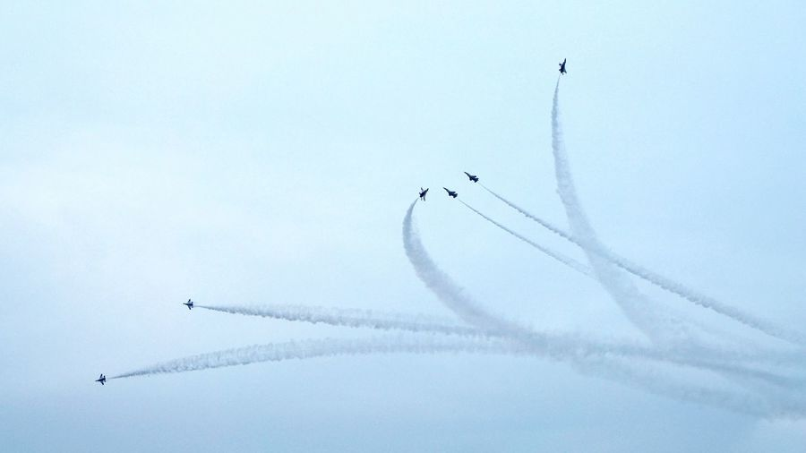 Low angle view of airplanes with trails in flight