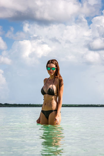 Young Woman Wearing Sunglasses While Standing In Sea Against Cloudy Sky