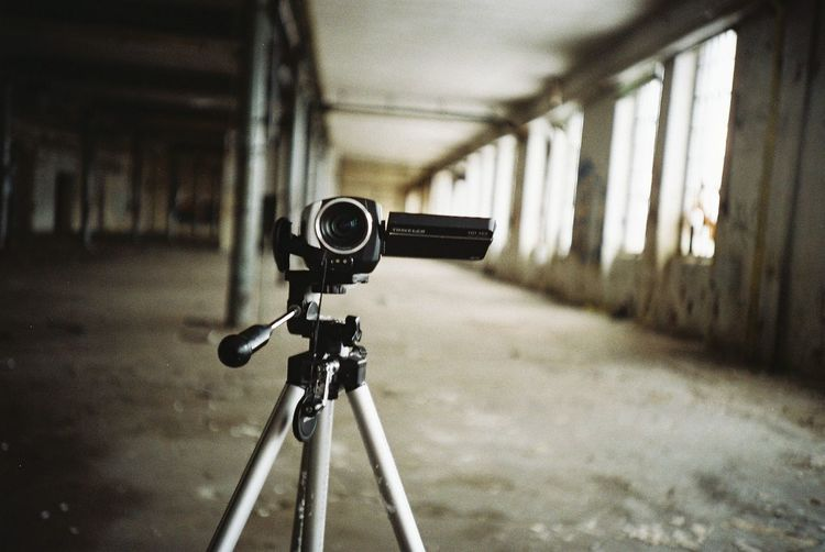 Close-up of video camera on tripod in abandoned building