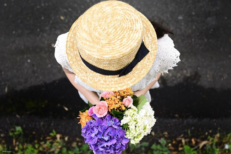 High Angle View Of Woman Holding Bouquet On Street