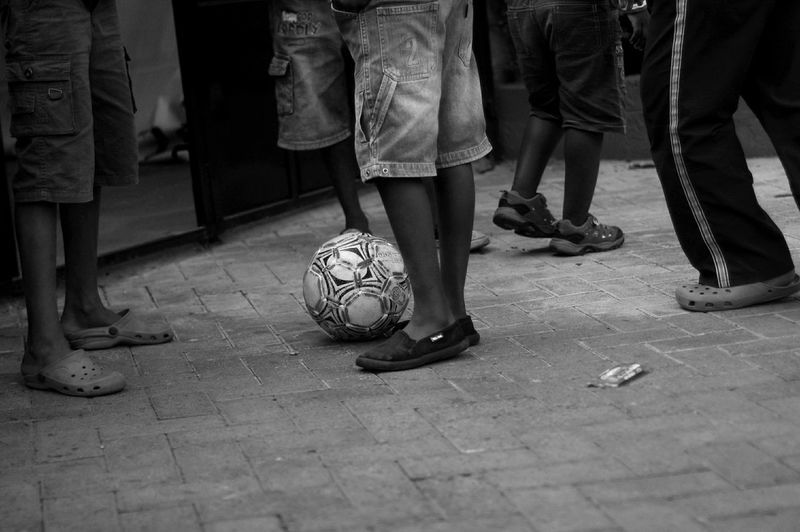 Low section of boys playing soccer in street