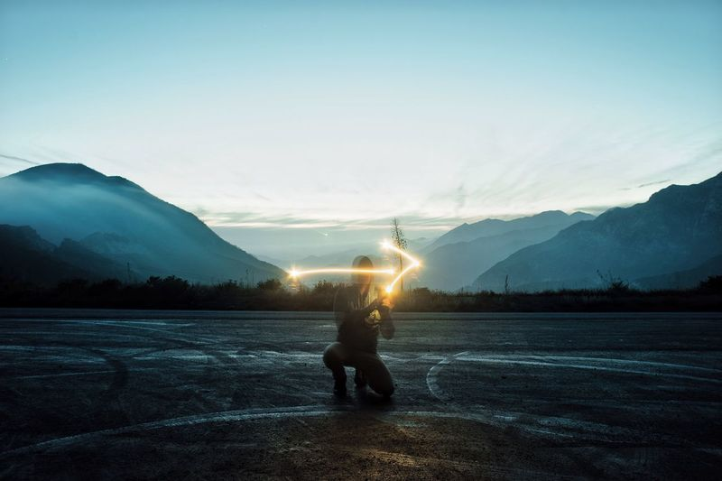 Man Light Painting An Arrow Before Mountain Landscape