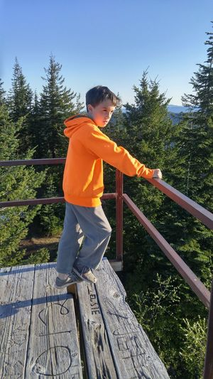 Boy Standing By Railing Against Clear Sky