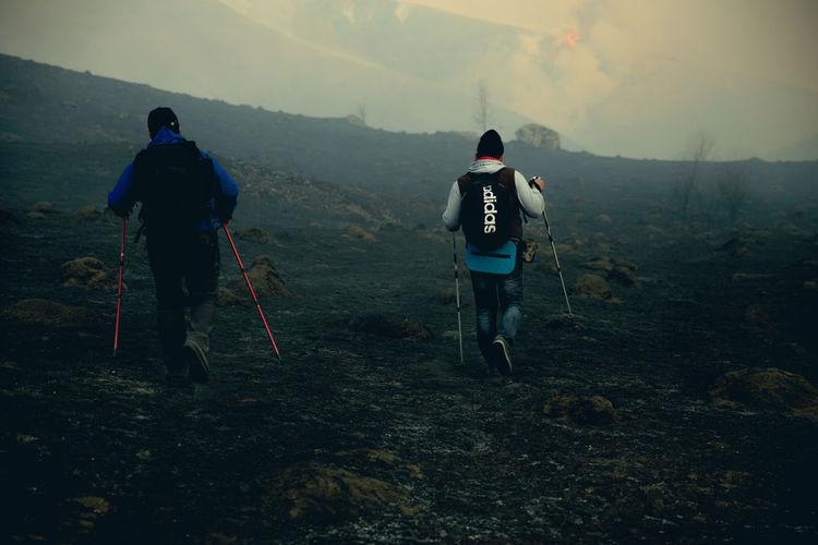 Rear view of men walking on mountain against sky