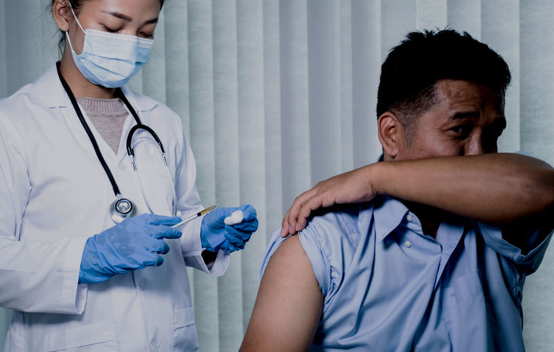 Young doctor wearing mask vaccinating patient in clinic