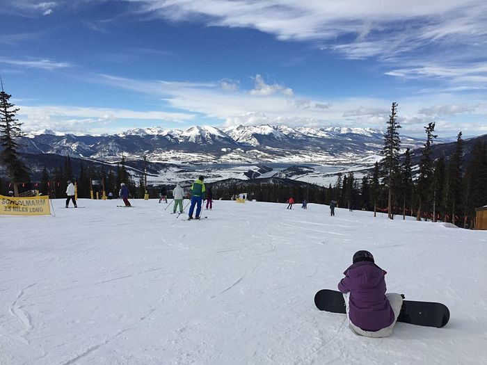 View of people skiing on snowcapped mountain