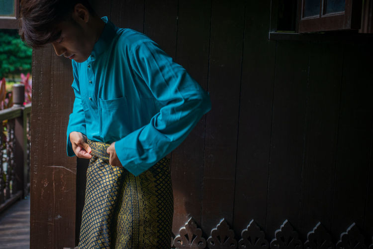 Side view of young man wearing sampin in traditional clothing in a malay wooden house during eid.