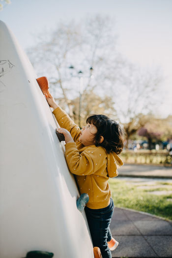 Side view of child climbing wall at playground