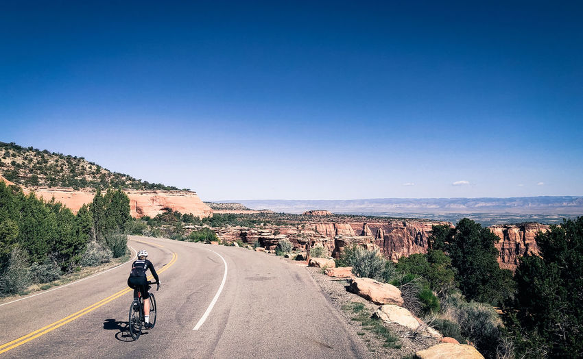 A cyclist rides through Colorado National Monument, near Grand Junction, Colorado. Sky Road Transportation Bicycle The Way Forward Direction One Person Nature Real People Sunlight Beauty In Nature Outdoors Riding Colorado National Monument Desert Bicycling Cycling Road Clear Sky Adventure Recreational Pursuit Diminishing Perspective Mode Of Transportation Rear View Day Lifestyles Copy Space