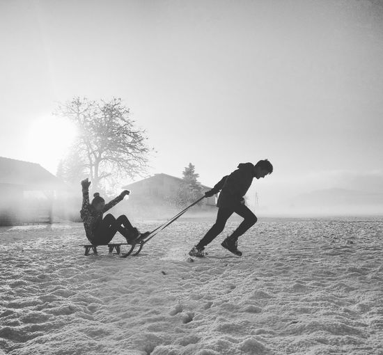 Brother Pulling Sister On Sled At Snow Covered Field Against Sky