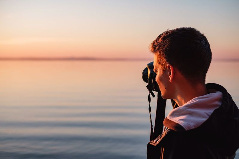 Young Man Photographing Sea Against Sky During Sunset