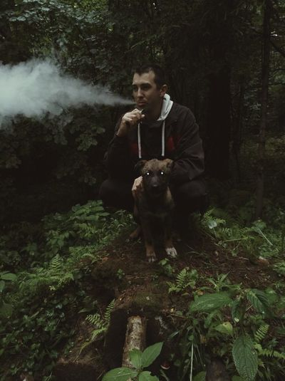 Man exhaling smoke while crouching by dog on field