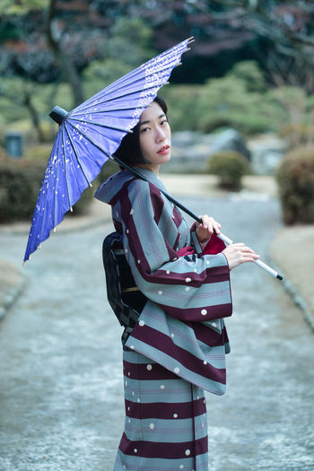 Woman with umbrella standing in water