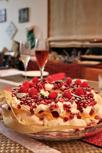Close-up of fruit pavlova and wine served on table