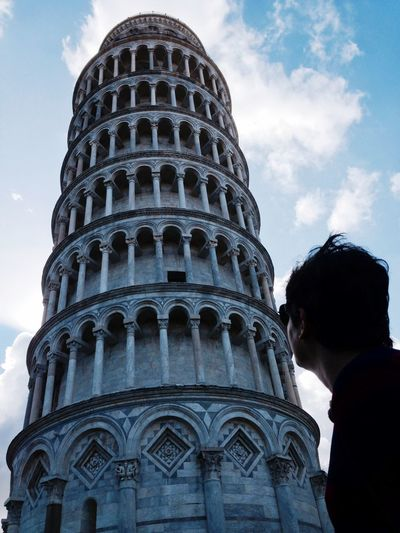 Low angle view of man standing by leaning tower of pisa