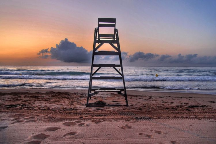 Lifeguard tower on beach against sky during sunset