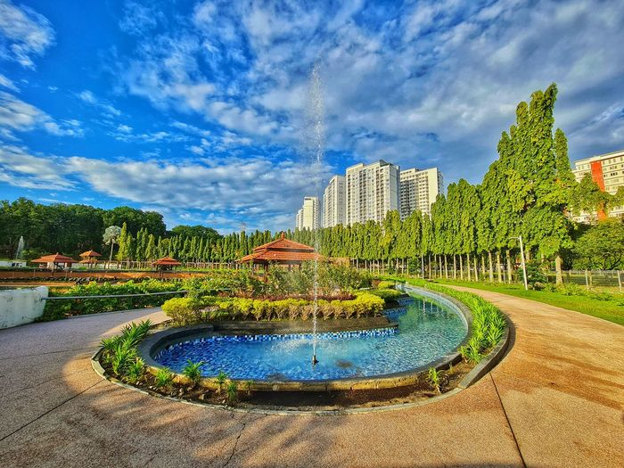 Fountain in park by buildings against blue sky