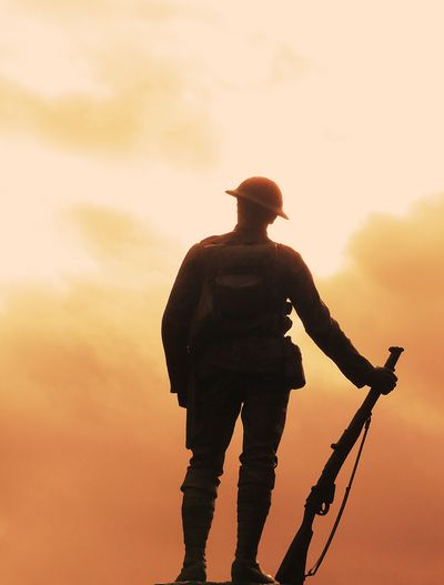 Statue of army soldier with riffle against sky during sunset