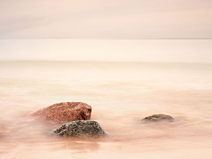 Long exposure of sea and big boulders sticking up. pink sunset at rocky coast of balsitc sea.