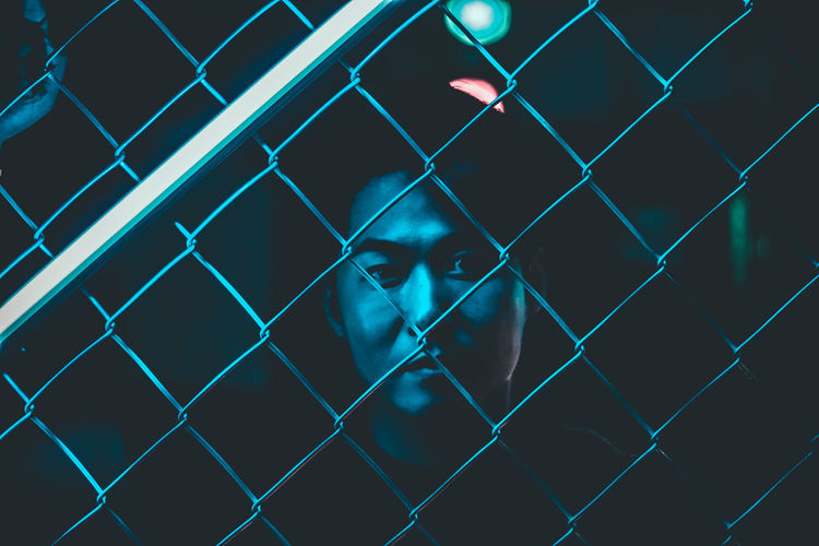 Close-up portrait of man seen through chainlink fence at night